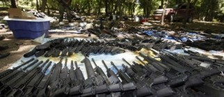 Soldiers display seized weapons after raid on drug hitmen near Higueras
