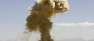 A cloud of dust and debris from a controlled detonation rise into the air outside the FOB Shank in Logar Province in Afghanistan