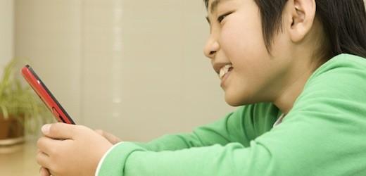 携帯電話のメールを見ている子供