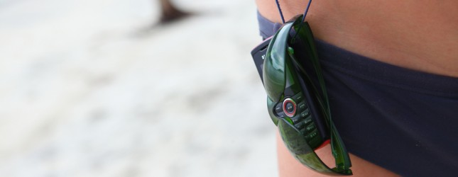 Minimalist beach gear  sunglasses and mobile phone worn on a sling by paul keller