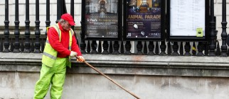 A council cleaner sweeps dirt and debris