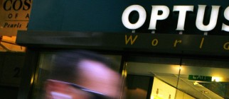 Sydney shoppers walk past an Optus telec