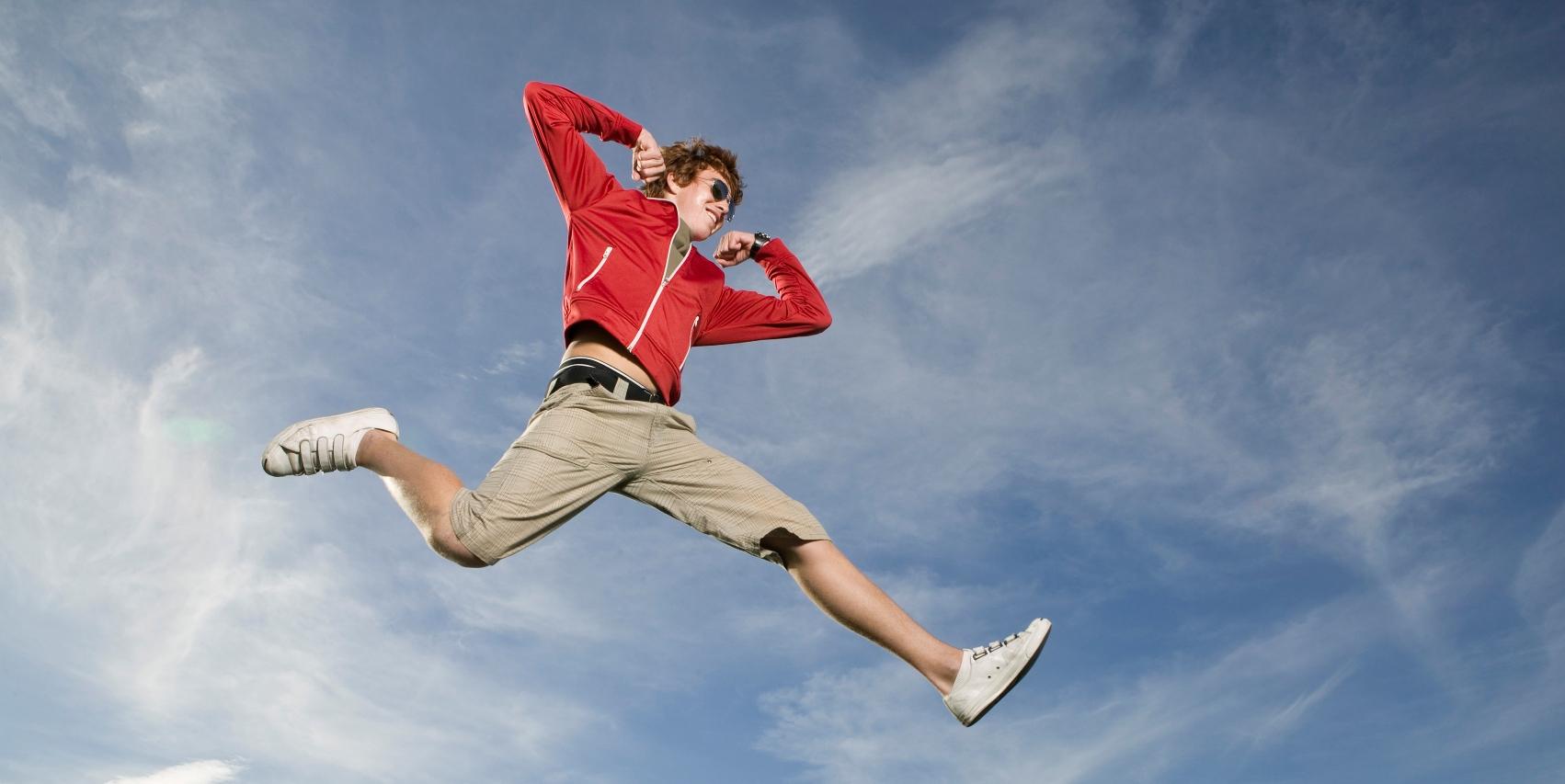 Teenage boy leaping in midair