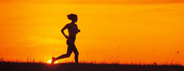 Silhouette of woman jogging at sunrise or sunset