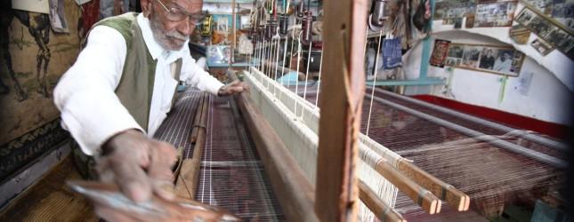 An elderly Libyan artisan produces tradi