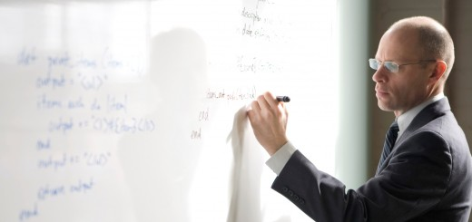Businessman writing on whiteboard, side view