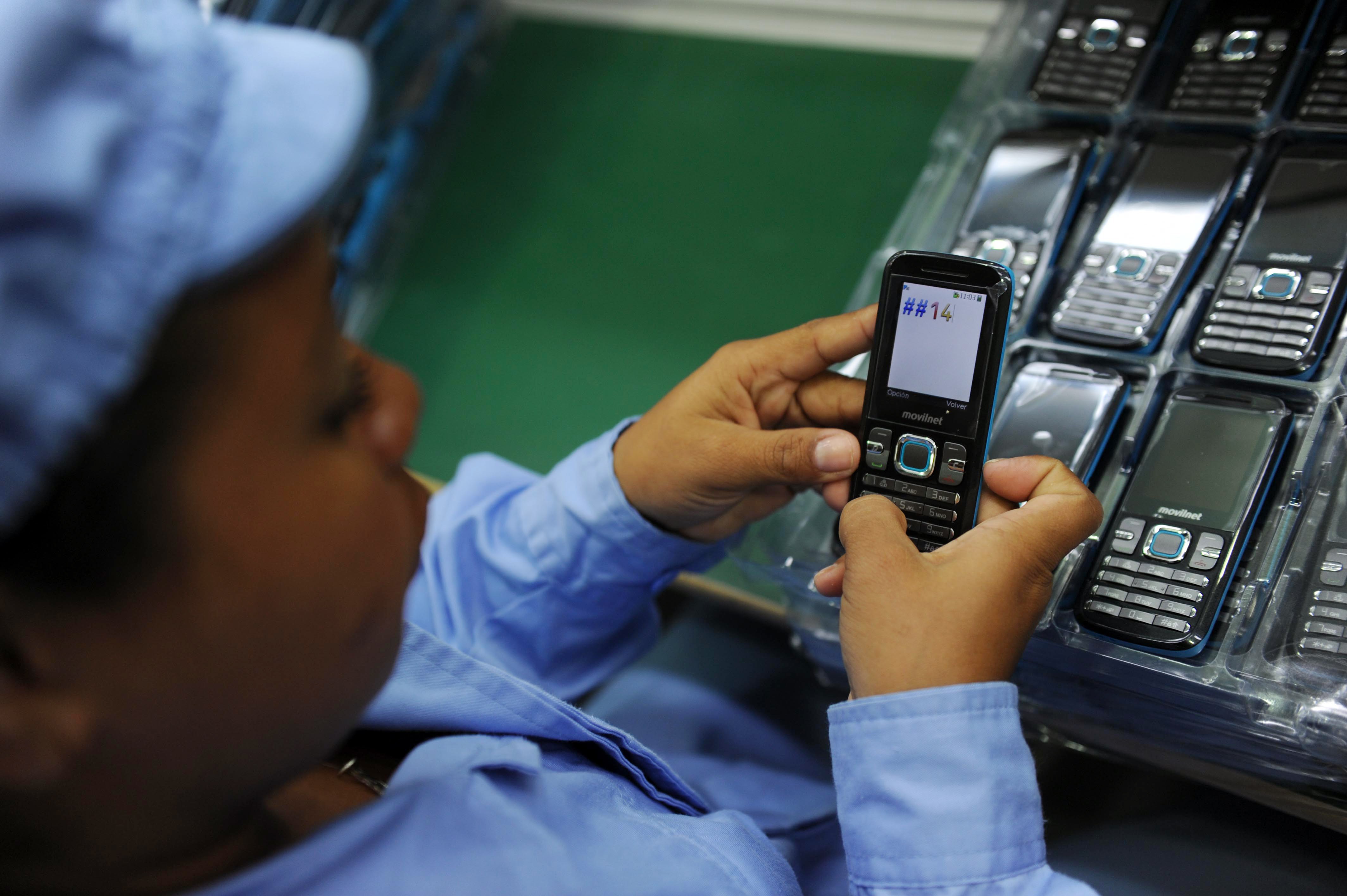 A worker tests cell phones made in China
