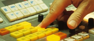 Finger pushing button on Video Editing desk, TV studios, Spain, close-up