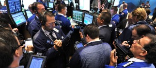 Traders crowd around a post on the floor