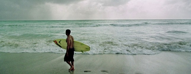 A surfer walks along the beach in South Miami Beac