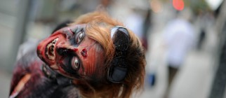 An actress portraying a zombie poses for