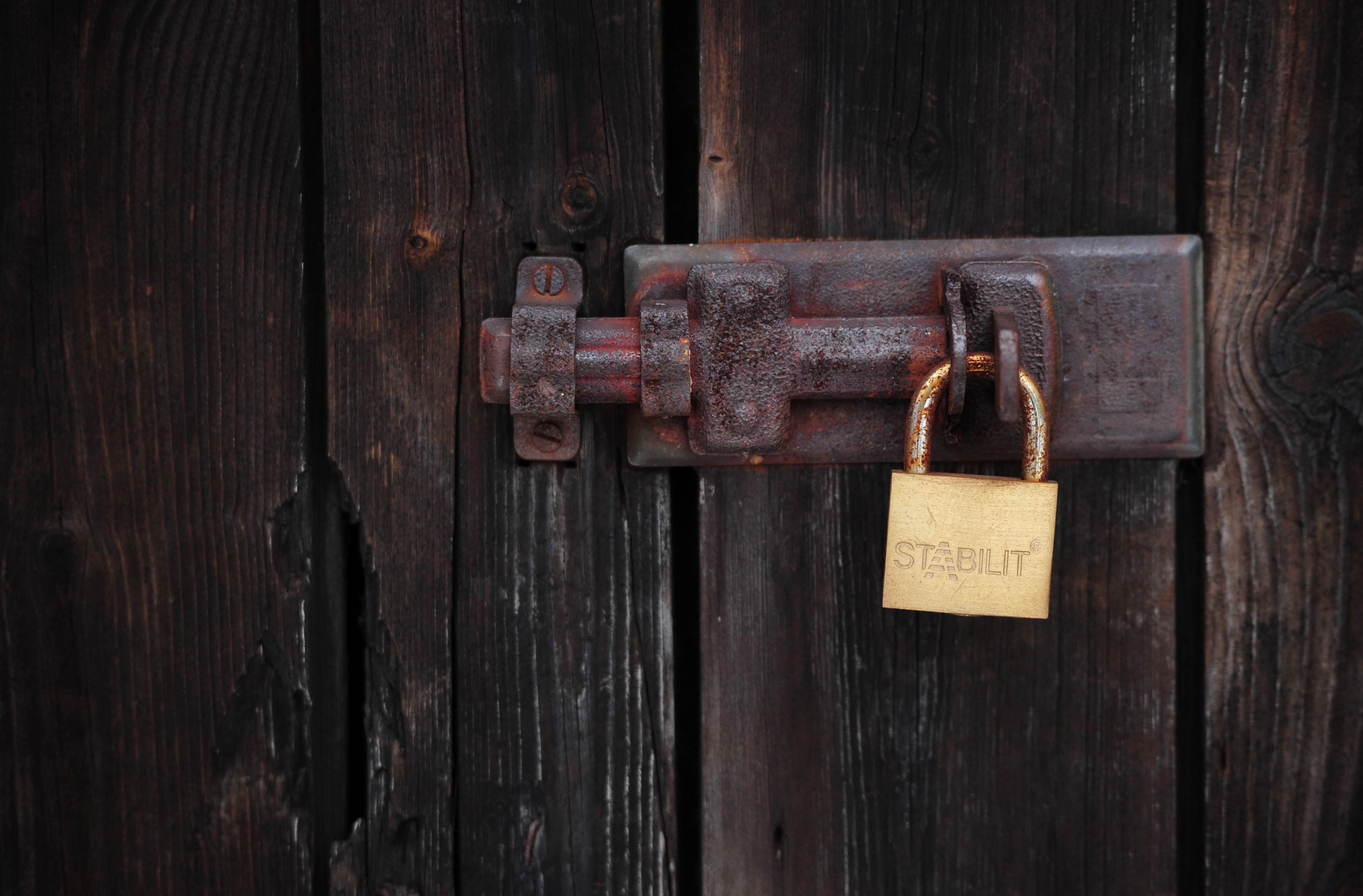 A padlock closes a wooden door at a grav