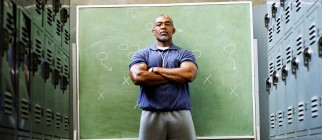 Coach in locker room, standing in front of chalkboard