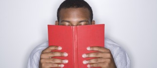Young man reading a book in the library
