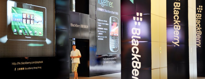 A man walks past a large BlackBerry adve