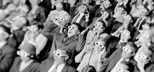 High angle view of a group of spectators sitting in a movie theater wearing 3-D glasses