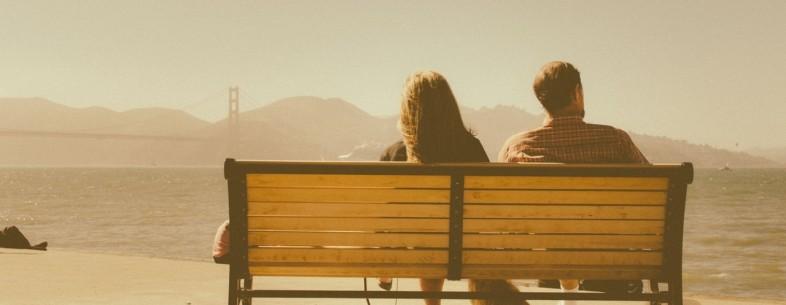 couple sitting by bridge
