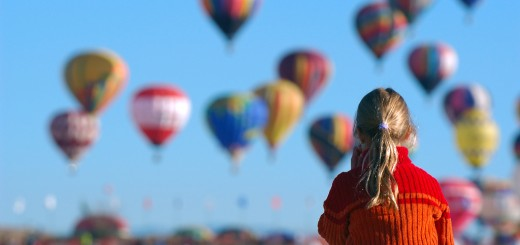 girl watching balloons in crowd