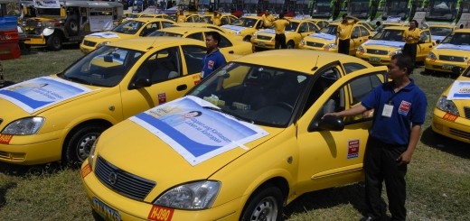 Drivers stand beside modified taxis and