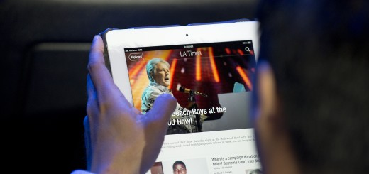 An attendee reads a Los Angeles Times ne
