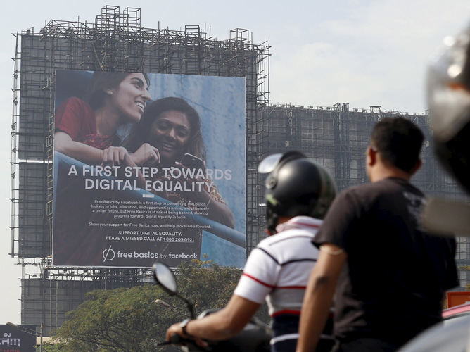 Motorists ride past a billboard displaying Facebook's Free Basics initiative in Mumbai, India